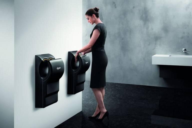 Femme en train de sécher les mains dans un sèche-mains airblade Dyson