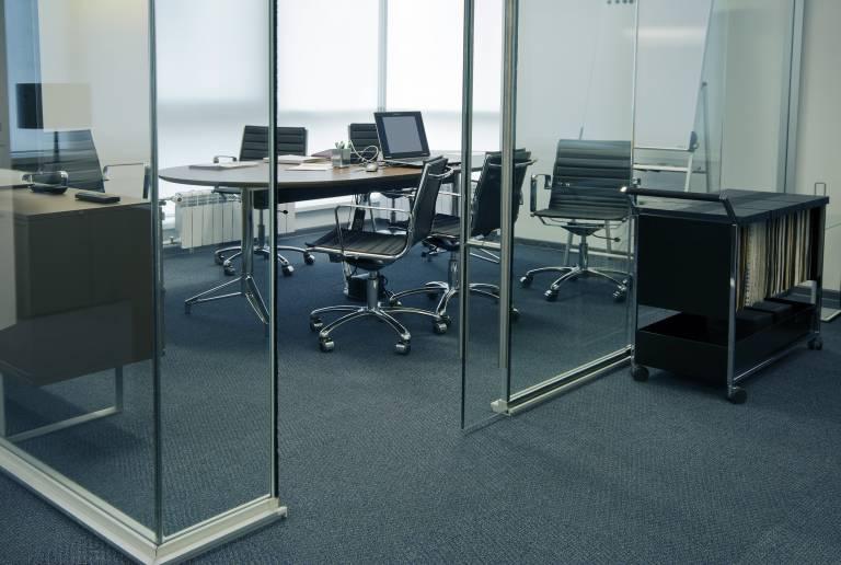 Bureau dans espace vitré avec moquette foncée chinée