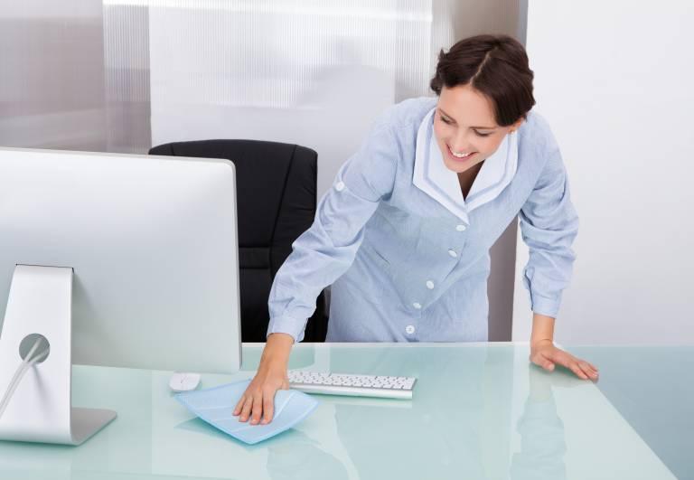 Femme nettoyant le dessus d'un bureau avec un chiffon