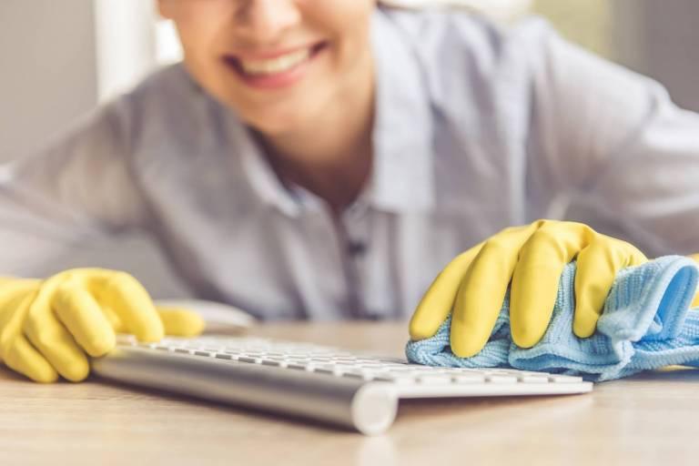 Femme nettoyant un clavier avec des gants de protection et un chiffon