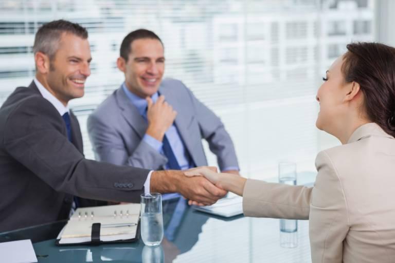 Homme et femme se serrant la main autour d'un bureau