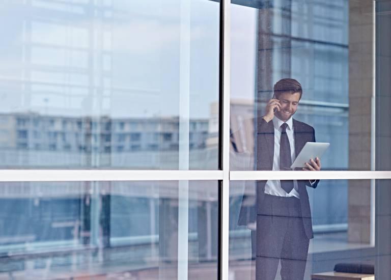 Homme d'affaires téléphonant derrière une vitre d'immeuble