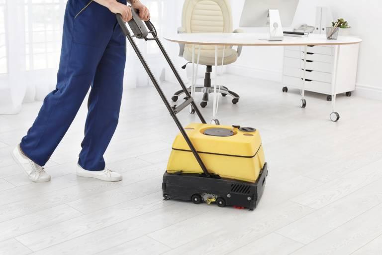 Homme nettoyant le sol d'un bureau avec une machine