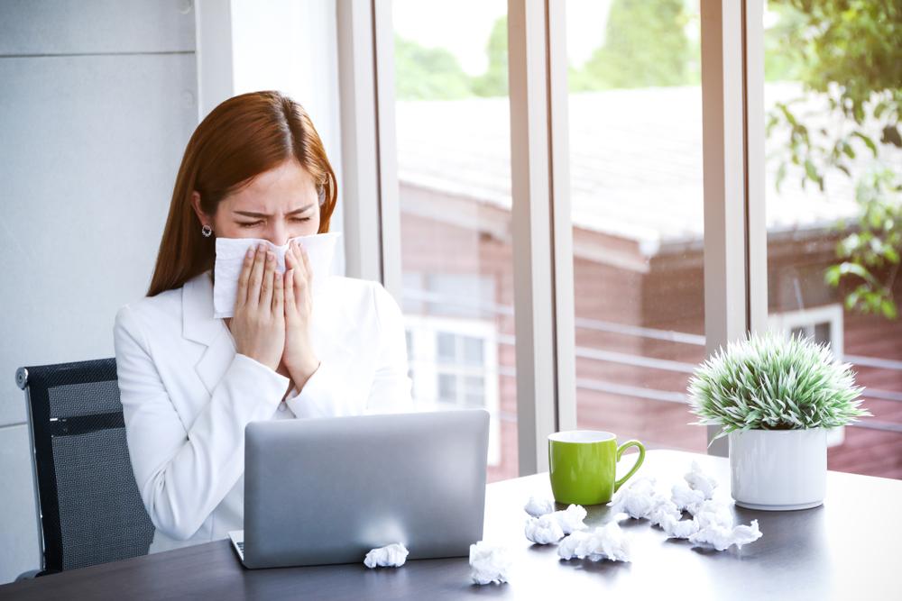 jeune femme au bureau allergique se mouchant dans un mouchoir en papier