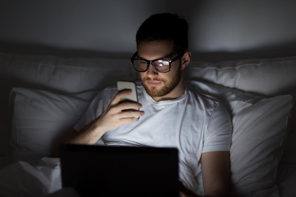 homme jeune avec des lunettes au lit la nuit avec un ordinateur portable et un smartphone